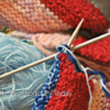 a close-up of a knitting project and a blue roll of yarn