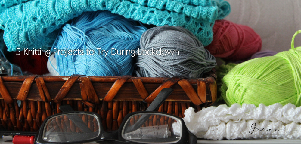Basket with knitted wool items with a pair of glasses